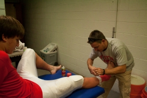 Brandon Stafford tapes freshman Luke McCleary's ankle before a JV football game.