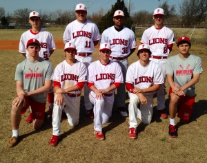 The seniors on the baseball team laugh while trying to hide Zane Smith's uniform mistake. Smith wore gray pants instead of white. (Photo courtesy of Andy Postema)