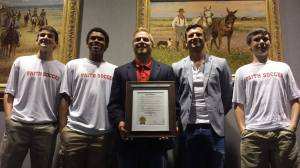 Sophomore soccer players receive a proclamation from Grapevine Mayor William D. Tate celebrating their fourth straight title alongside their coaches. (Photo courtesy of Grapevine Faith Athletic Department)