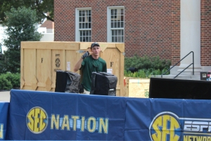 An SEC Network crew member moves a crate containing parts of the set for SEC Nation.